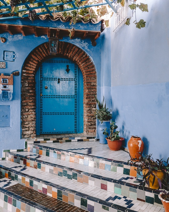 Small door and tiled stairs in Chefchaouen by Dancing the Earth