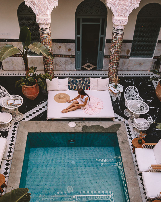 Relaxing on the sun lounger near the pool of riad Ksar Kasbah in Marrakesh by Dancing the Earth