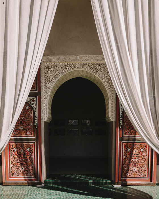 A door framed with curtains in the secret garden of Marrakesh by Dancing the Earth