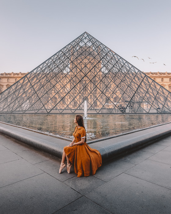 Sitting on the side of the Louvre pyramid by Dancing the Earth